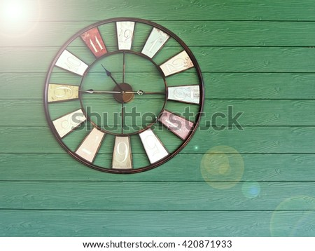 Old vintage with flare clock on green wooden plank wall background. Time management concept. - stock photo