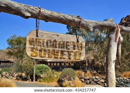 "old vintage wood signboard with text "" welcome to Soweto"" hanging on a branch - stock photo"