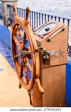 Old Vintage Wooden Helm Wheel near Blue Ovcean - stock photo