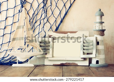 old vintage wooden white frame, lighthouse and sailing boat on wooden table. vintage filtered image. nautical lifestyle concept  - stock photo