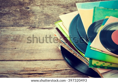 Old vinyl record on wooden background. Retro toned.