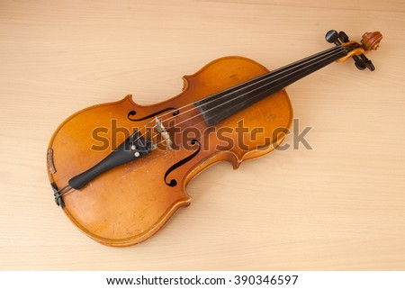 Old violin music concept lying on wood desk - stock photo