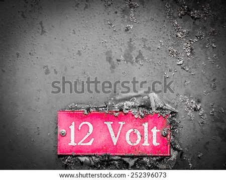 old 12 volt signage on grunge metal - stock photo