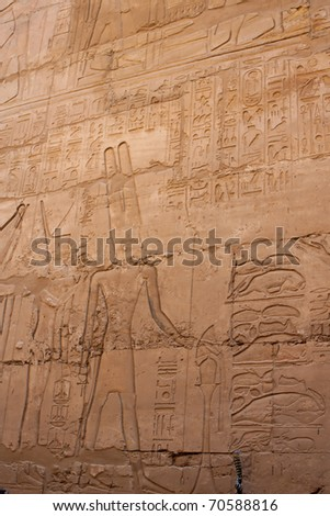 Old wall in the Karnak temple with ancient images. - stock photo