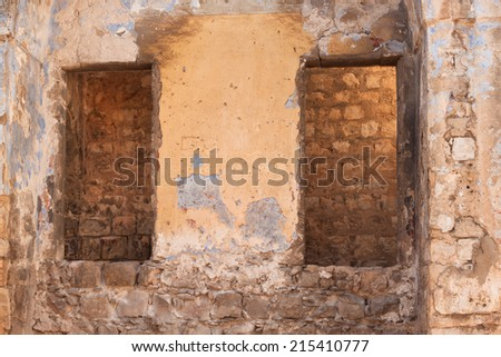 Old wall of a ruined house with openings for windows - stock photo