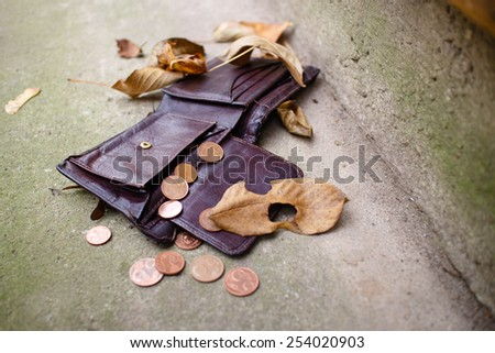Old wallet with euro coins on concrete floor. - stock photo