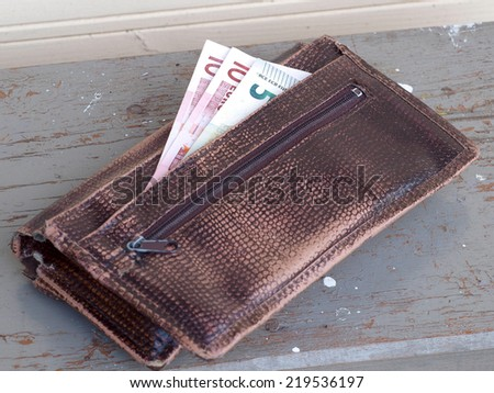 Old wallet with some euro banknotes on wooden bench       - stock photo