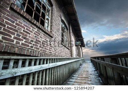 Old warehouse with broken windows and a walkway - stock photo