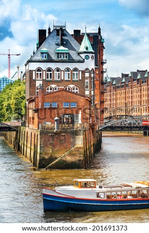 Old warehouses and a tourist boat in Speicherstadt, Hamburg - stock photo