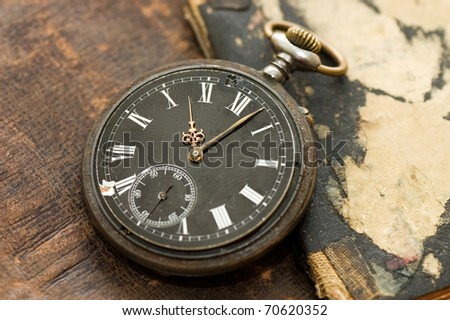 Old watch on the book - stock photo