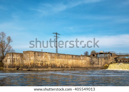 Old water gate of the abandoned hydroelectric power plant - stock photo
