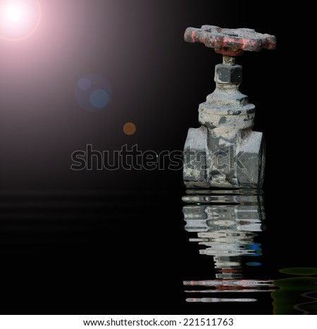 Old Water valve with reflected in water - stock photo
