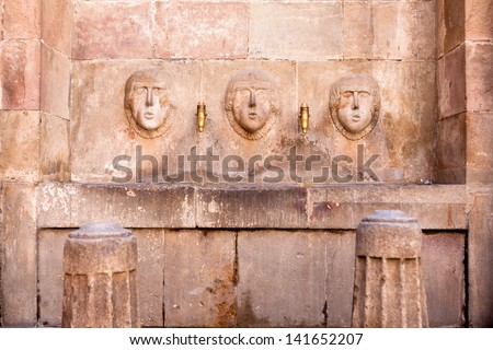 old watering place - drinking fountain - 3 faces made of stone - stock photo