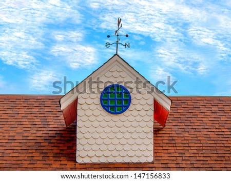 Old weather vane on roof top - stock photo