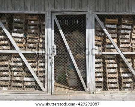 old weathered barn on backyard with empty wooden crates - stock photo