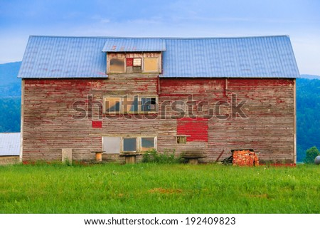 Old weathered barn with peeling red paint in Stowe, Vermont, USA - stock photo