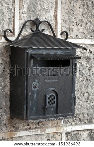 Old weathered black metal mailbox mounted on gray stone wall - stock photo