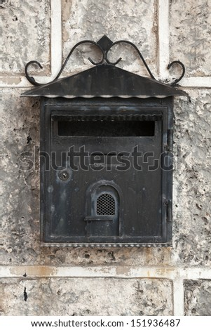 Old weathered black metal mailbox mounted on gray stone wall. Front view - stock photo