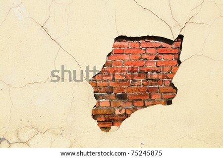 Old weathered brick and stucco wall fragment - stock photo