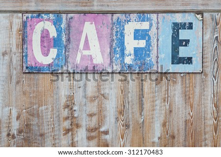 Old weathered cafe sign on distressed rustic wood wall - stock photo