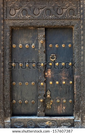 Old weathered door of building in Stone Town, Zanzibar, Tanzania - stock photo