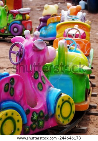 old weathered fancy train driving by a small electric motor locomotive in a children playground as circus carousel in a country fair in BANGKOK THAILAND.  - stock photo