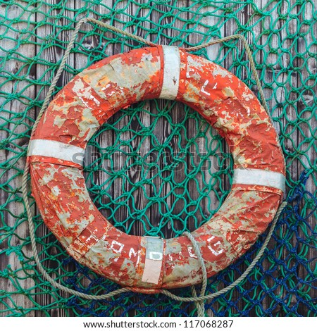 Old weathered lifebuoy on wooden wall with fishing net - stock photo