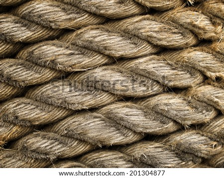 Old weathered rope worn down to expose individual strands - stock photo