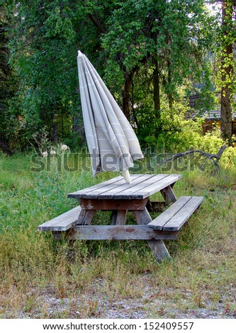 old weathered umbrella and picnic table - stock photo