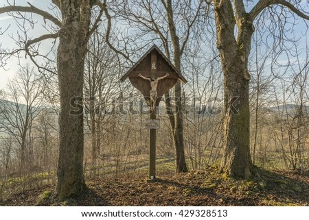 Old weathered wayside cross in the middle of two trees in bavarian forest - stock photo