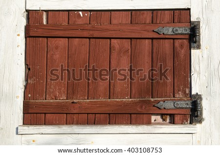 Old weathered window shutter made of red planks - stock photo