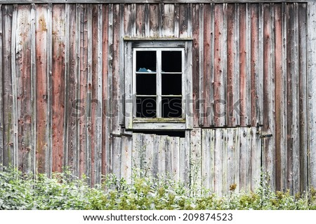 Old weathered wooden building with crashed window - stock photo