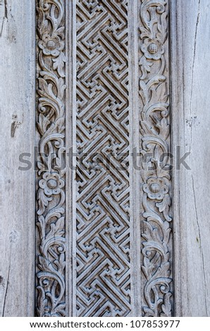 Old weathered wooden wall decoration with carved ornament - stock photo