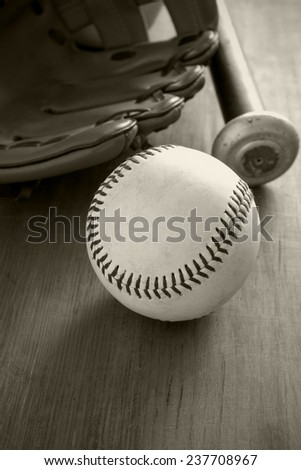 Old well used baseball with mitt and bat in black and white sepia tint  - stock photo
