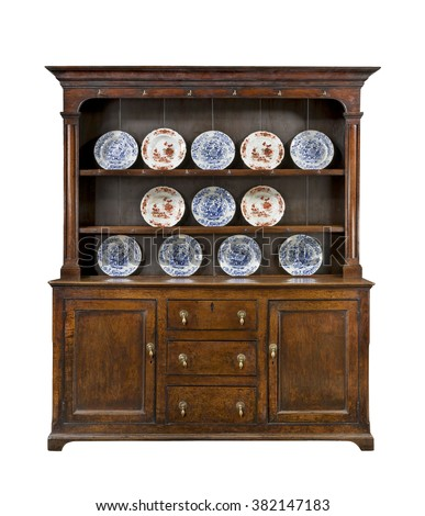 Old Welsh dresser cupboard sideboard in oak with plates isolated on white with clipping path - stock photo