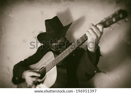 Old West Cowboy Playing Guitar. A cowboy playing a guitar, edited in vintage film style. - stock photo