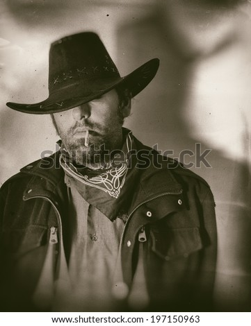 Old West Cowboy Smoker Wide. An old west cowboy smoking a hand rolled cigarette, edited in vintage film style. - stock photo