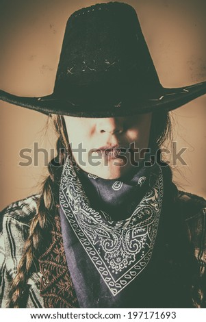 Old West Cowgirl Hat Low. Old west cowgirl with hat low blocking eyes, edited in vintage film style. - stock photo