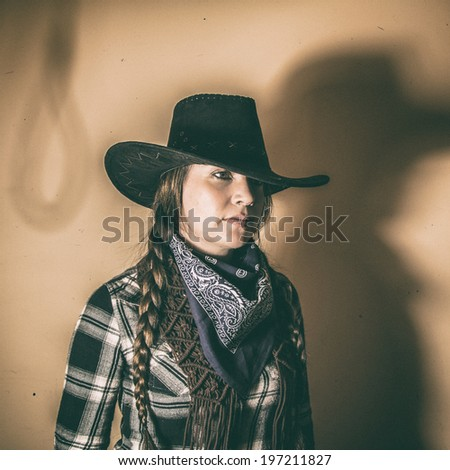 Old West Cowgirl Noose Shadow. Old west cowgirl with hat shadow of a noose, edited in vintage film style. - stock photo