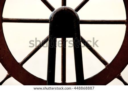 Old wheel of a sail boat in a harbor - stock photo