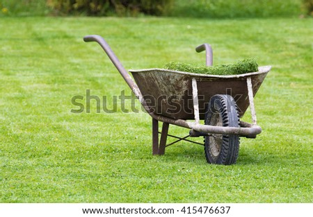 Old wheelbarrow on a lawn with fresh grass clippings in summer - stock photo
