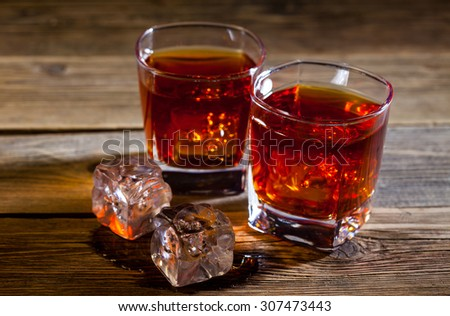 old whiskey with ice on aged surface of table - stock photo