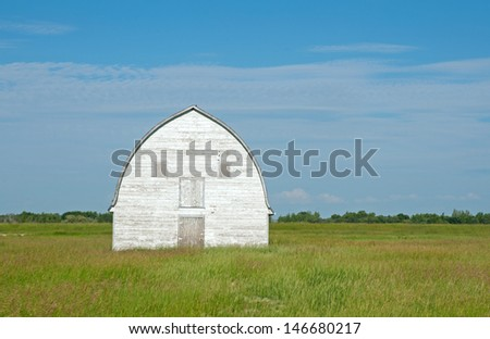 Old white barn in meadow in Manitoba, Canada - stock photo