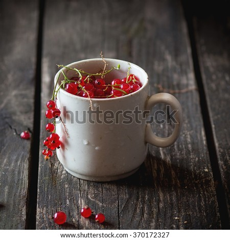 Old white cup full of fresh ripe red currant over old wooden table. Dark rustic style. Natural day light. Square image with selective focus - stock photo