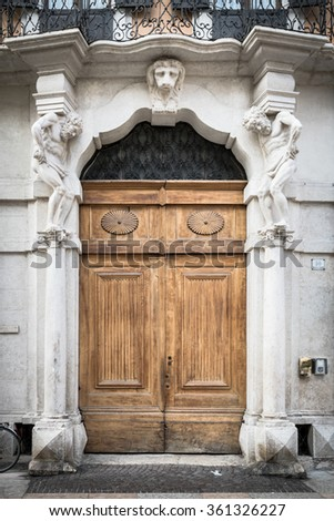 Old white stone entrance and wooden portal with statues that support the side columns. - stock photo