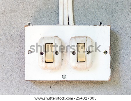 Old white switch on the wall of countryside house. - stock photo