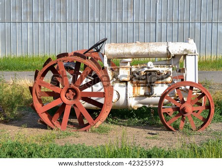 Old white tractor rusting away in old farm equipment graveyard - stock photo