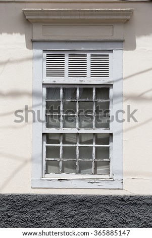 old white window in facade of house - stock photo