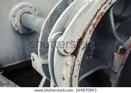Old winch fragment with big shaft. Selective focus and shallow DOF - stock photo