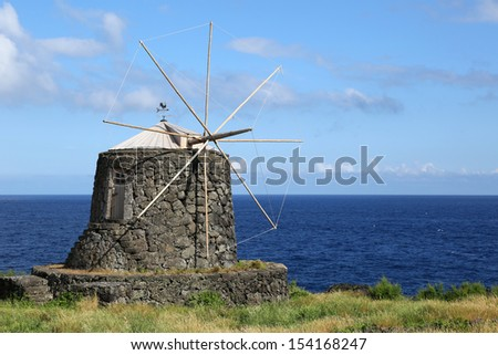 Old windmill and Atlantic Ocean on the island of Corvo Azores Portugal - stock photo